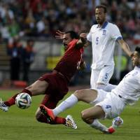 Photo - Portugal's Hugo Almeida, left, lunges for the ball against Greece's Kostas Manolas during a friendly soccer match between Portugal and Greece at the National stadium, in Oeiras, near Lisbon, Saturday, May 31, 2014. The game is a warm-up match for both teams ahead the upcoming World Cup in Brazil. (AP Photo/Francisco Seco)