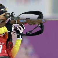 Photo - Germany's Evi Sachenbacher-Stehle shoots during the mixed biathlon relay at the 2014 Winter Olympics, Wednesday, Feb. 19, 2014, in Krasnaya Polyana, Russia. (AP Photo/Lee Jin-man)
