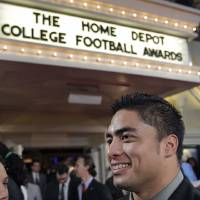 Photo - Notre Dame's Manti Te'o talks with reporters as he arrives at the Home Depot College Football Awards in Lake Buena Vista, Fla., Thursday, Dec. 6, 2012.(AP Photo/John Raoux)