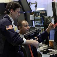 Photo - In this Friday, Dec. 14, 2012,  photo, Traders Patrick McKeon, left, and Joel Lucchese work on the floor of the New York Stock Exchange. Stocks rose modestly Monday, Dec. 17, 2012, on Wall Street. Investors were encouraged by signs of progress in talks to avoid the