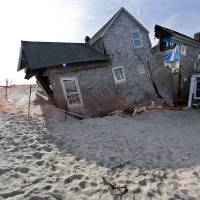 Photo - FILE - In this Jan. 3, 2013 photo, a beach front home that was severely damaged by Superstorm Sandy rests in the sand in Bay Head, N.J.   (AP Photo/Mel Evans)