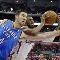 Photo - Oklahoma City Thunder forward Nick Collison (4) and Los Angeles Clippers guard Chris Paul (3) tangle in the second half of an NBA basketball game in Los Angeles, Sunday, March 3, 2013. The Thunder won 108-104. (AP Photo/Reed Saxon)