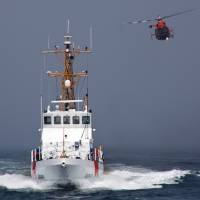 Photo - CORRECTS DATE OF CRASH TO SUNDAY, NOT MONDAY - In this Aug. 29, 2011 photo provided by the U.S. Coast Guard, a Rescue Helicopter from Airs Station Los Angeles conducts a close fly-by of the Coast Guard Cutter Halibut. A smuggler's vessel rammed a small U.S. Coast Guard boat deployed by the cutter Halibut, off the Southern California coast early Sunday Dec. 2, 2012, killing one Coast Guard member and injuring another, authorities said. The cutter was conducting an investigation into suspected smuggling near the Channel Islands west of Malibu. (AP Photo/U.S. Coast Guard/Steve Lee)
