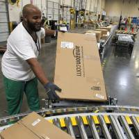 Photo - FILE - In this Nov. 11, 2010 file photo, Leacroft Green places a package to the correct shipping area at an Amazon.com fulfillment center, in Goodyear, Ariz. Amazon is teaming up with the U.S. Postal Service to deliver packages on Sundays. The Seattle company said Monday, Nov. 11, 2013, that  Sunday delivery will be available this week to customers in the New York and Los Angeles metropolitan areas. Amazon and the Postal Service plan to roll out service to