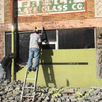 Photo -  Green painted brick concealed the original cast stone and blond brick facade at 2415 N Walker Ave. The building is being renovated to become the home of Pizzeria Gusto, part of The Rise, an upscale shopping center in Uptown.    -  Provided