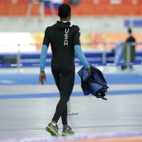 Photo - Shani Davis of the U.S. walks holding his jacket after competing in the men's speedskating team pursuit quarterfinals at the Adler Arena Skating Center during the 2014 Winter Olympics in Sochi, Russia, Friday, Feb. 21, 2014.  (AP Photo/Matt Dunham)