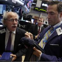 Photo - Traders Peter Tuchman, left, and Gregory Rowe work on the floor of the New York Stock Exchange Wednesday, Oct. 9, 2013. World stock markets were dragged down Friday Oct. 25,2013 by doubts about the durability of recoveries in Asia's two biggest economies. (AP Photo/Richard Drew)