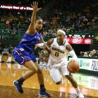 Photo - Baylor guard Odyssey Sims (0), right, drives on Kansas guard Dakota Gonzalez (2), left, in the first half of an NCAA college basketball game on Sunday, Jan. 5, 2014, in Waco, Texas. (AP Photo/Rod Aydelotte)