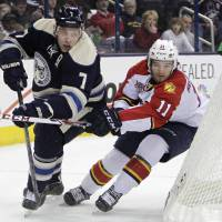 Photo - Columbus Blue Jackets' Jack Johnson, left, clears the puck as Florida Panthers' Jonathan Huberdeau defends during the first period of an NHL hockey game on Saturday, Feb. 1, 2014, in Columbus, Ohio. (AP Photo/Jay LaPrete)
