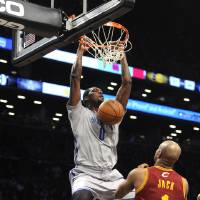 Photo - Brooklyn Nets' Andray Blatche (0) dunks in front of Cleveland Cavaliers' Jarrett Jack (1) during the first half of an NBA basketball game Friday, March 28, 2014, in New York. (AP Photo/Kathy Kmonicek)