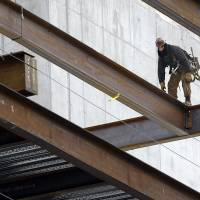 Photo - In this Tuesday, April 29, 2014 photo, a worker positions iron girders at a building construction site, in Boston. The Labor Department releases first-quarter productivity data on Wednesday, May 7, 2014. (AP Photo/Steven Senne)