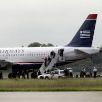 Photo -   Passengers walk off a US Airways flight at Philadelphia International Airport, after the plane returned to the airport, Thursday, Sept. 6, 2012, in Philadelphia. Airport spokeswoman Victoria Lupica says US Airways Flight 1267 returned to the airport Thursday morning as a