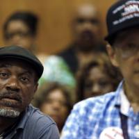 Photo - FILE - In this July 22, 2013, file photo, Tony Brown, left, a Department of Transportation retiree, listens to union leaders talk about what Detroit's bankruptcy filing means to thousands of retirees during a meeting in Detroit. Monday, Aug. 19, 2013, is the deadline for a host of banks, bond insurers, two employee pension systems and others standing to lose big if a federal judge declares Detroit insolvent to legally file their objections to the largest municipal bankruptcy in U.S. history.  (AP Photo/Paul Sancya, File)