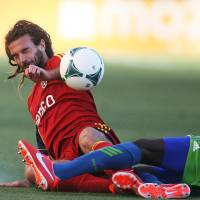 Photo - Real Salt Lake midfielder Kyle Beckerman, left, collides with Seattle Sounders FC defender Djimi Traore during the first half of an MLS soccer game at Rio Tinto Stadium in Sandy, Utah, on Saturday, June 22, 2013. (AP Photo/The Salt Lake Tribune, Kim Raff)  DESERET NEWS OUT; LOCAL TV OUT; MAGS OUT.