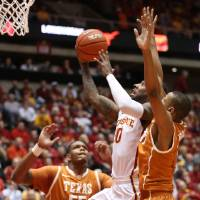 Photo - Iowa State guard DeAndre Kane goes past Texas' Cameron Ridley and Demarcus Holland, right, during the first half of an NCAA college basketball game at Hilton Coliseum in Ames, Iowa, Tuesday, Feb. 18, 2014. Iowa State won 85-76. (AP Photo/Justin Hayworth)