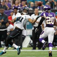 Photo -   Jacksonville Jaguars wide receiver Laurent Robinson, left, makes a reception over Minnesota Vikings cornerback Chris Cook, right, during the first half of an NFL football game on Sunday, Sept. 9, 2012, in Minneapolis. (AP Photo/Genevieve Ross)