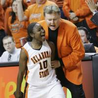 Photo - Oklahoma State University guard Andrea Riley, left, celebrates with head coach Kurt Budke, right, near the end of a women's college basketball game against the University of Oklahoma in Stillwater, Okla., Saturday, Jan. 12, 2008. Riley had 45 points as OSU defeated OU 82-63. (AP Photo/Sue Ogrocki)