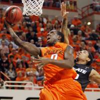 Photo - OSU's Jean-Paul Olukemi (0) takes a shot in front of Rodney McGruder (22) of KSU during the men's college basketball game between Oklahoma State University (OSU) and Kansas State University (KSU) at Gallagher-Iba Arena in Stillwater, Okla., Saturday, January 8, 2011. Photo by Nate Billings, The Oklahoman