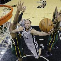 Photo - San Antonio Spurs' Manu Ginobili (20), of Argentina, shoots around Utah Jazz's Derrick Favors (15) during the first half of an NBA basketball game, Sunday, March 16, 2014, in San Antonio. (AP Photo/Eric Gay)