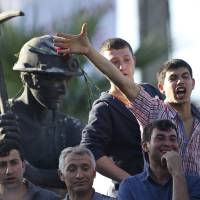 Photo - Anti-government protesters chant slogans on a monument for the town's miners, during a march in Soma, Turkey where the mine accident took place, Friday, May 16, 2014. Hundreds of protesters took part in the march against the government and there were clashes with the police forces. An explosion and fire at a coal mine in Soma, some 250 kilometers (155 miles) south of Istanbul, killed hundreds of workers, authorities said, in one of the worst mining disasters in Turkish history. (AP Photo/Lefteris Pitarakis)