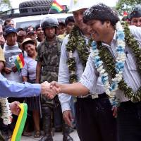 Photo - FILE - In this Dec. 14, 2006 file photo provided by the Bolivia's Presidential Press Office, Bolivia's President Evo Morales, right, shakes hands with U.S. ambassador Philip Goldberg during the inauguration of part of a road sponsored by the U.S. Agency for International Development (USAID) in the tropical region of El Sillar, Cochabamba, Bolivia. Morales said Wednesday, May 1, 2013 he is expelling the USAID from Bolivia for allegedly seeking to undermine his leftist government. (AP Photo/Noah Friedman Rudovsky, Bolivian Presidency, File)