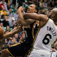 Photo - Indiana Pacers guard George Hill, left, is fouled by Utah Jazz guard Jamaal Tinsley (6) whike driving to the basket in the first half during an NBA basketball game on Saturday, Jan. 26, 2013, in Salt Lake City. (AP Photo/Steve C. Wilson)