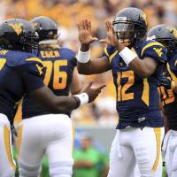 Photo - West Virginia quaterback Geno Smith (12) calls a play from the sidelines during their NCAA college football against Marshall in Morgantown, W.Va., Saturday, Sept. 1, 2012. West Virginia won 69-34. (AP Photo/Christopher Jackson)