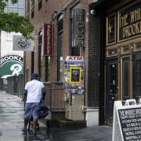 Photo - In this July 1, 2013 photo, restaurants line the street adjacent to the Brooklyn Brewery, in the Williamsburg section of the Brooklyn borough of New York. In rundown urban neighborhoods across the country, craft breweries helped transform the neighborhoods around them, drawing young new residents and other small businesses. (AP Photo/Richard Drew)