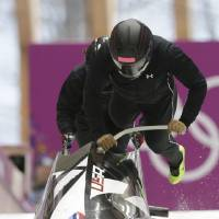 Photo - The team from the United States USA-1, piloted by Elana Meyers, start a run during a women's bobsleigh training session at the 2014 Winter Olympics, Saturday, Feb. 15, 2014, in Krasnaya Polyana, Russia. (AP Photo/Dita Alangkara)