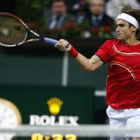 Photo -   Spain's David Ferrer returns a ball to Czech Republic's Tomas Berdych during their Davis Cup finals tennis match in Prague, Czech Republic, Sunday, Nov. 18, 2012. (AP Photo/Petr David Josek)