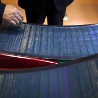 Photo - Company executives look at thin-film solar panels developed by MiaSole before a press conference held at the headquarters of Hanergy Group in Beijing, China, Wednesday, Jan. 9, 2013. Hanergy Group, the Chinese company that bought MiaSole, a California producer of thin-film solar panels, said it can make a success of the emerging technology where others have suffered huge losses. (AP Photo/Alexander F. Yuan)