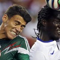 Photo - Mexico defender Hector Moreno, left, tries to keep Portugal forward Eder away from the ball during the first half of their friendly soccer match in Foxborough, Mass., Friday, June 6, 2014. (AP Photo/Charles Krupa)