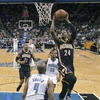 Photo - Indiana Pacers' Paul George (24) shoots between Orlando Magic's DeQuan Jones (20) and Arron Afflalo (4) during the first half of an NBA basketball game, Wednesday, Jan. 16, 2013, in Orlando, Fla. (AP Photo/John Raoux)