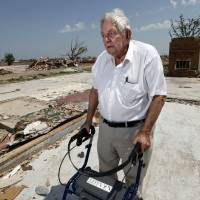 Photo - John Roady stands with his new walker, which he received from an organization replacing storm survivors' lost medical equipment. Roady and his wife Helen lost their home in Moore on May 20.  STEVE SISNEY - THE OKLAHOMAN