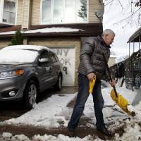 Photo -   Gennady Naydis keeps clearing his driveway even as the handle breaks off his shovel in the New Dorp section of Staten Island, N.Y., Thursday, Nov. 8, 2012. The New York-New Jersey region woke up to a layer of wet snow and more power outages after a new storm pushed back efforts to recover from Superstorm Sandy. (AP Photo/Seth Wenig)