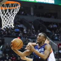 Photo - Charlotte Bobcats' Kemba Walker (15) is fouled under the basket by Portland Trail Blazers' Meyers Leonard during the first half of an NBA  basketball game in Portland, Ore., Monday, March 4, 2013. (AP Photo/Greg Wahl-Stephens)