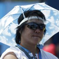 Photo - A spectator watches second round matches at the Australian Open tennis championship as temperatures are expected to top 44 C (112 F) in Melbourne, Australia, Thursday, Jan. 16, 2014. (AP Photo/Mark Baker)