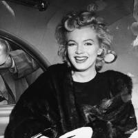 Photo - FILE - In this June 2, unknown year, file photo, actress Marilyn Monroe smiles in a car after arriving tousled from an all-night plane flight from Hollywood to Idlewild Airport, in New York. The actress said she planned to rest in New York before going to England to make a new movie with Sir Laurence Olivier. In late 2012, the FBI has released a new version of files it kept on Monroe that reveal the names of some of her acquaintances who had drawn concern from government officials and members of her entourage over their suspected ties to communism. (AP Photo, File)