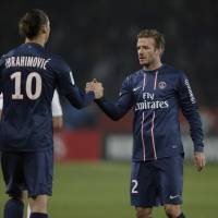 Photo - Paris Saint Germain's Zlatan Ibrahimovic from Sweden shakes hands with David Beckham after their League One soccer match between PSG and Montpellier at Parc des Princes Stadium, in Paris, Friday March 29, 2013. (AP Photo/Francois Mori)