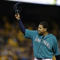 Photo - Seattle Mariners starting pitcher Felix Hernandez tips his cap to fans as he leaves a baseball game against the Oakland Athletics in the eighth inning, Friday, April 11, 2014, in Seattle. Hernandez struck out 11 batters and allowed no runs. (AP Photo/Ted S. Warren)