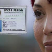 Photo -   Transsexual Daniel Walter Alvarez shows his police credential outside Congress in Buenos Aires, Argentina, Wednesday, May 9, 2012. Argentina's Congress is set to approve on Wednesday the Gender Identity Law, which allows citizens to change their gender in public records, including birth certificates and national identity cards. (AP Photo/Natacha Pisarenko)