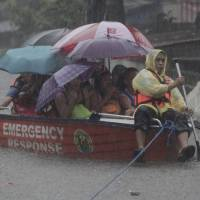Photo - A man uses a boat Wednesday to carry people across a flooded street in San Juan, east of Manila, Philippines. Widespread flooding that paralyzed the Philippine capital began to ease Wednesday as rescue efforts focused on a large number of distressed residents, some still marooned on their roofs. AP Photo