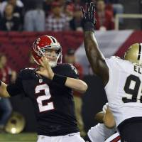 Photo - Atlanta Falcons quarterback Matt Ryan (2) throws under pressure from New Orleans Saints defensive tackle Sedrick Ellis (98) during the first half of an NFL football game, Thursday, Nov. 29, 2012, in Atlanta. (AP Photo/Rich Addicks)