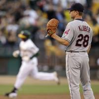 Photo -   Cleveland Indians' Corey Kluber, right, waits for Oakland Athletics' Yoenis Cespedes to run the bases on a two-run home run in the third inning of a baseball game Saturday, Aug. 18, 2012, in Oakland, Calif. (AP Photo/Ben Margot)