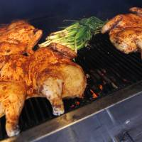 Photo - FOOD / OPEN FLAME / GRILL / GRILLING: Chickens and scallions cook on a grill during a cooking event at American Propane, 7401 Broadway Extension, in Oklahoma City, Thursday, April 14, 2011. Photo by Nate Billings, The Oklahoman ORG XMIT: KOD