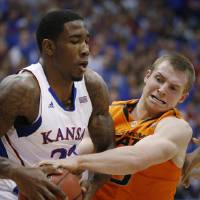 Photo - Kansas forward Jamari Traylor (31) keeps the ball away from Oklahoma State guard Phil Forte (13) during the first half of an NCAA college basketball game in Lawrence, Kan., Saturday, Feb. 2, 2013. (AP Photo/Orlin Wagner)
