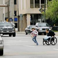 Photo - DOWNTOWN STREETS: A woman in a wheelchair and children hurry to cross N Walker between the County Courthouse and City Hall in downtown Oklahoma City  Thursday,  March 19, 2009.   BY JIM BECKEL, THE OKLAHOMAN ORG XMIT: KOD