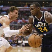 Photo - Utah Jazz forward Paul Millsap, right, drives to the basket around Los Angeles Clippers forward Blake Griffin during the first half of an NBA basketball game in Los Angeles, Saturday, Feb. 23, 2013. (AP Photo/Chris Carlson)
