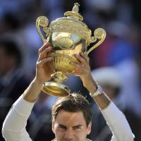 Photo - TENNIS:  Roger Federer of Switzerland holds the trophy aloft after defeating Andy Roddick of U.S. in their men's final match on the Centre Court at Wimbledon, Sunday, July 5, 2009. (AP Photo/Anja Niedringhaus)  ORG XMIT: XWIM338
