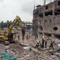 Photo - Bangladeshi workers and army personnel work to clean the debris and fallen ceiling of the garment factory building which collapsed in Savar near Dhaka, Bangladesh, Friday, May 10, 2013. The death toll from a garment factory building that collapsed more than two weeks ago near the Bangladeshi capital soared past 1,000 on Friday, with no end in sight to the stream of bodies being pulled from the wreckage of the worst-ever garment industry disaster. (AP Photo/Ismail Ferdous)